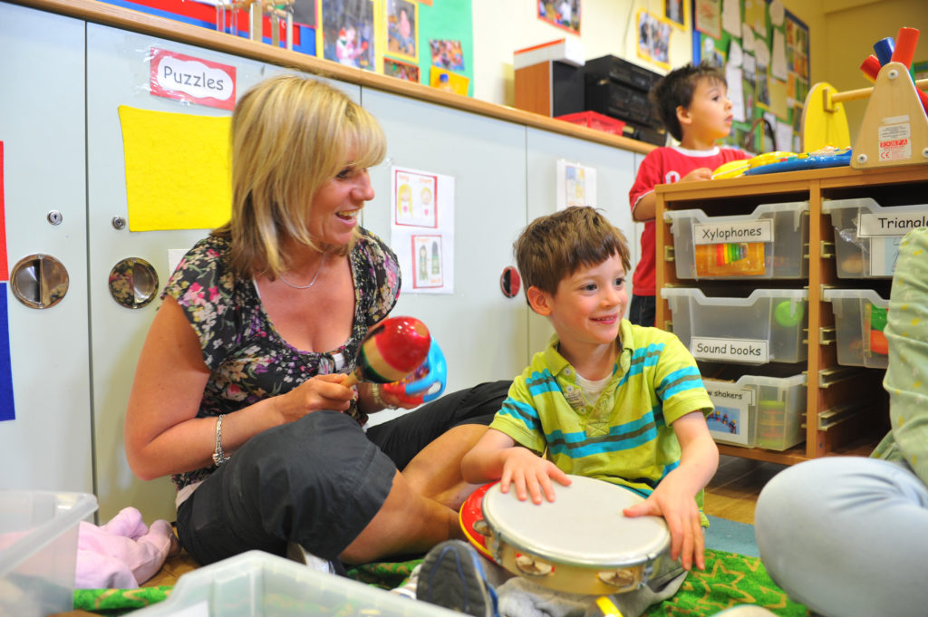 a child and teacher play with musical instruments