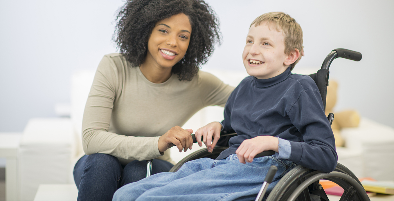 A nurse or caregiver is helping a boy with cerebral palsy get into his wheelchair. They are both smiling happily together.