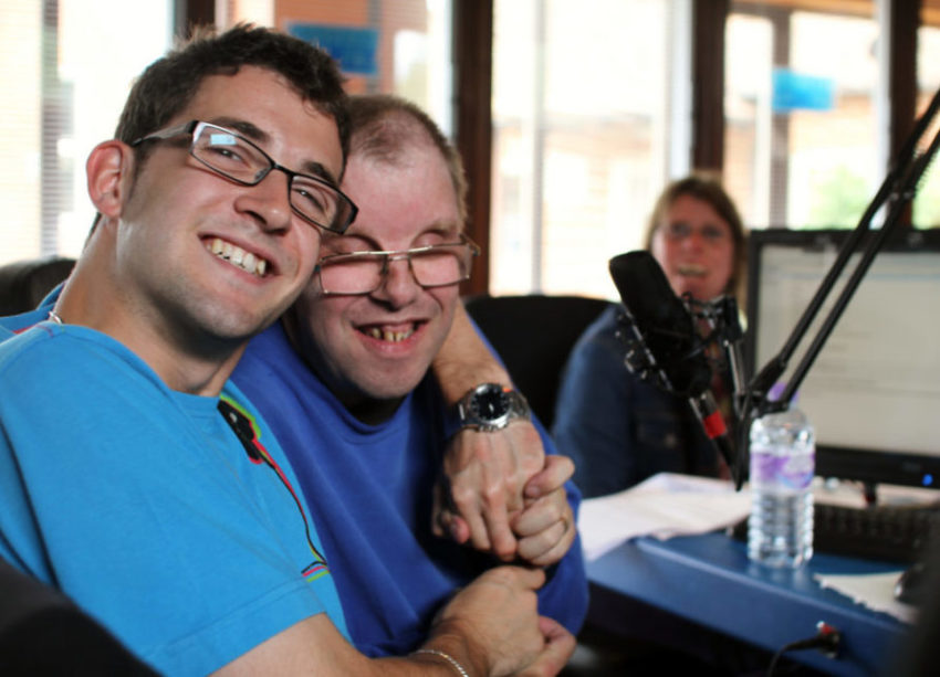 Two men with developmental disabilities conducting an interview and smiling