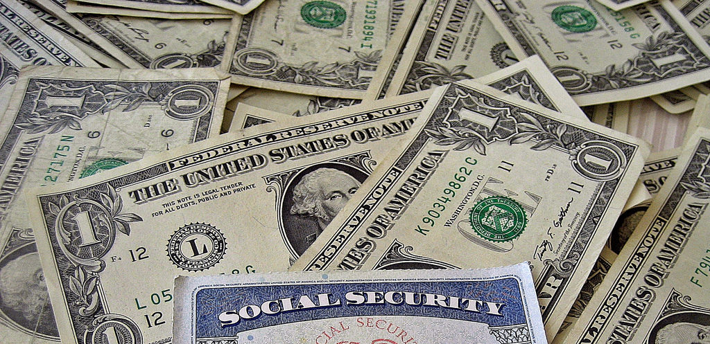Dollar bills scattered across a table with a social security card on top