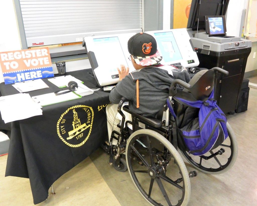 Participant using a wheelchair tests out the ballot marking machine