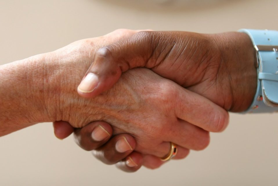 Two hands grasp each other in a handshake