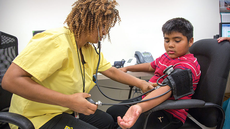 A nurse takes a young boys blood pressure