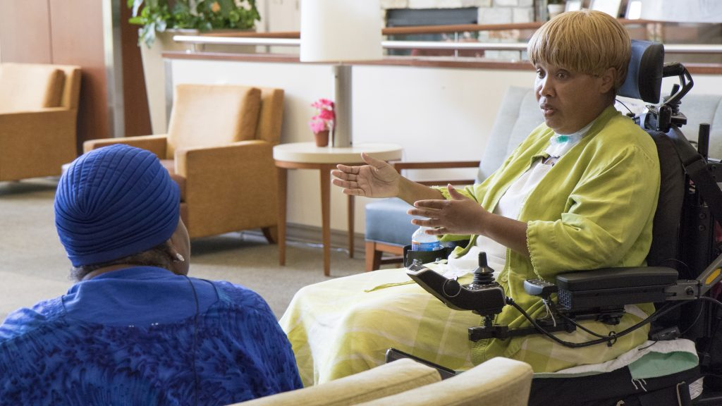 Ivis, sitting in a power wheelchair, sits to the right of a nursing home resident discussing discharge options.