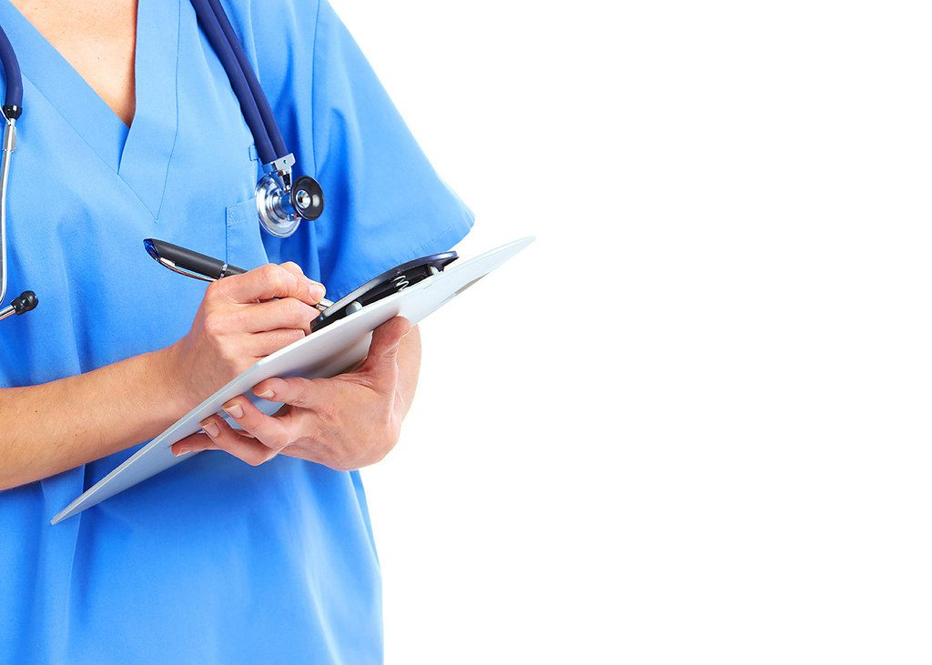 nurse wearing stethoscope holds a clipboard to write notes