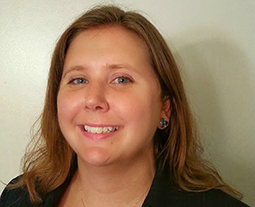 Portrait of Randi Ames, a white woman with blonde hair, in a black shirt against a cream-colored background