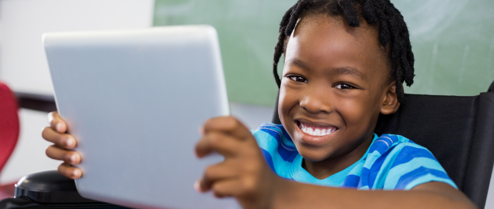 Young Black child in a wheelchair using a tablet for school