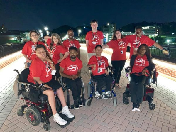 Disability Rights Maryland's Amity Lachowicz and other staff members of the 2018 Maryland Youth Leadership Forum pose for a group photo in matching red shirts on a lit bridge during nightfall.