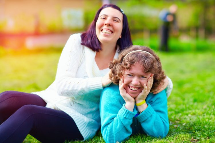 Two women lounging on a green lawn. They are both smiling, and one has her hands on the shoulders of the other.