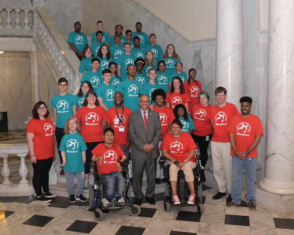 Staff and students of the 2018 Maryland Youth Leadership Forum pose for a group photo in matching red shirts with Lt. Governor Rutherford.